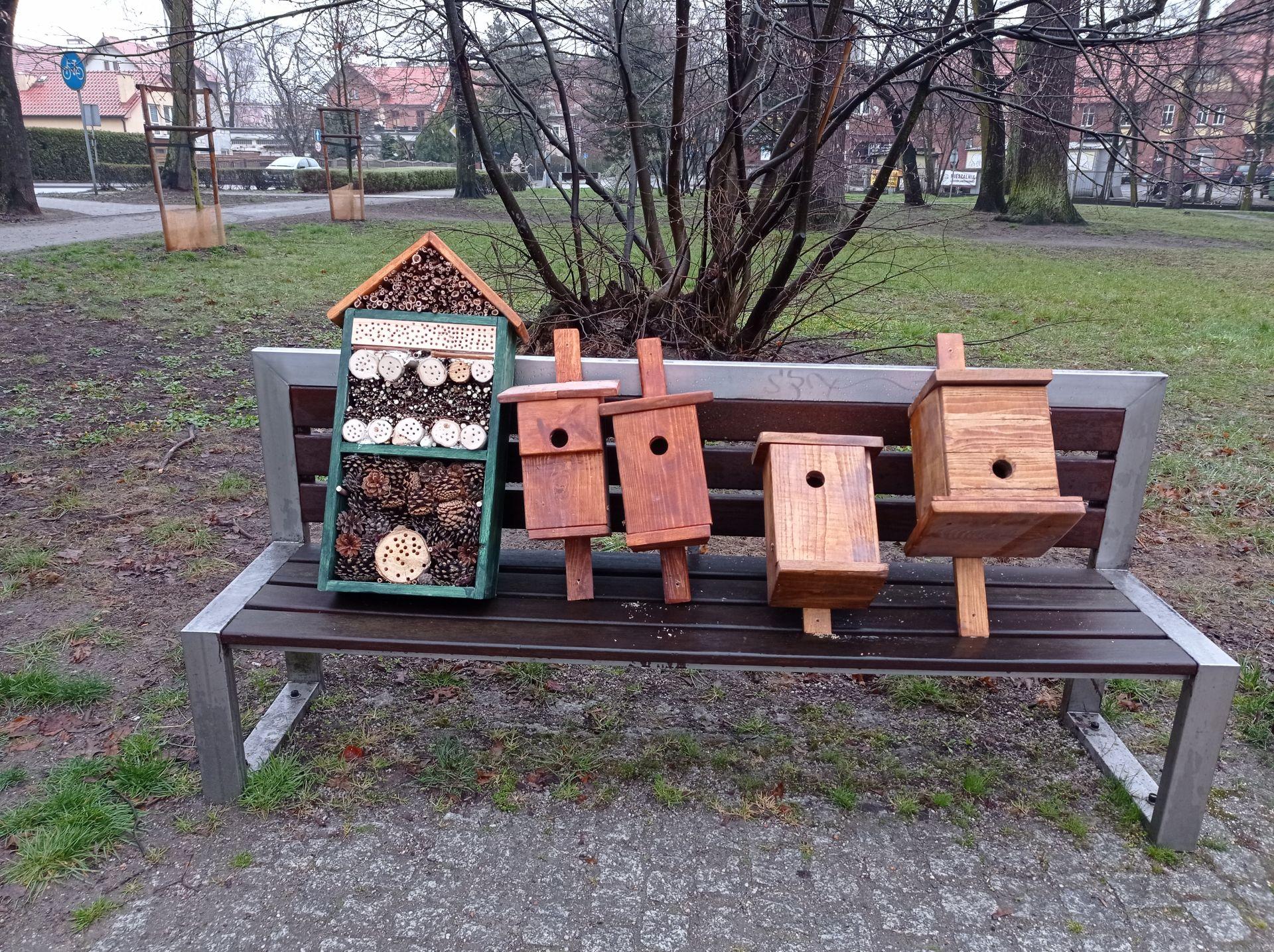 budki lęgowe i domki drewniane dla owadów leżące na ławce