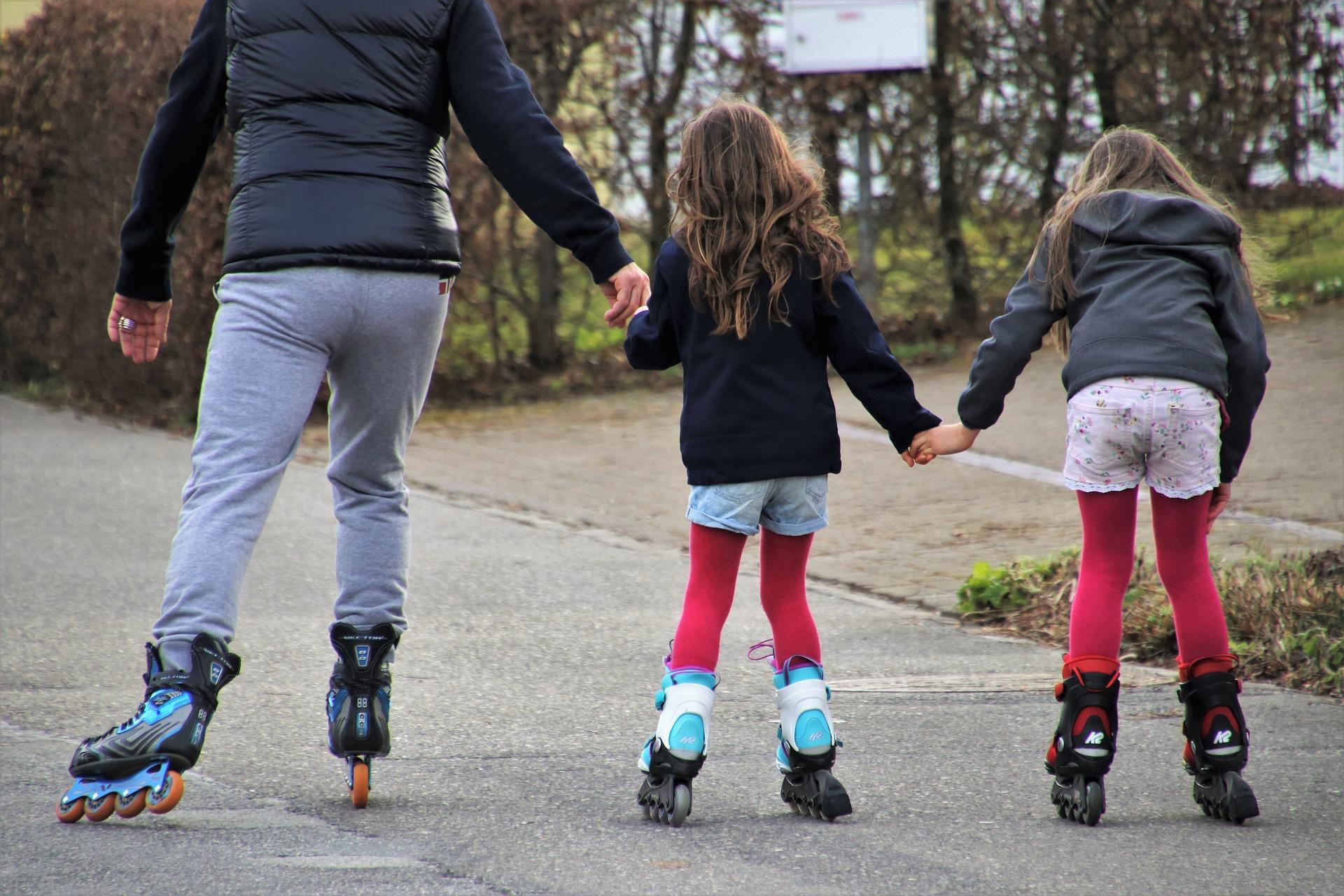 mężczyzna na rolkach z dwiema dziewczynkami, widać ich tyłem