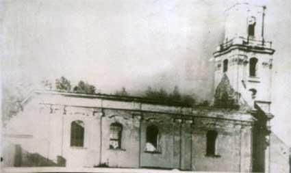 Wypalony kościół z zapadniętym dachem i spaloną wieżą.